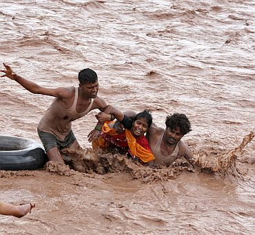 Rescuers help a woman to move a safer place from flooded Ghaghar river after heavy rains in Punchkula in Haryana on September 8