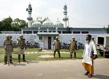 A priest walks past a mosque in Ayodhya