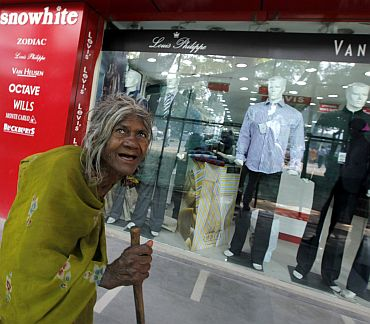 file photo shows a beggar walking past a shop window with designer clothes in New Delhi
