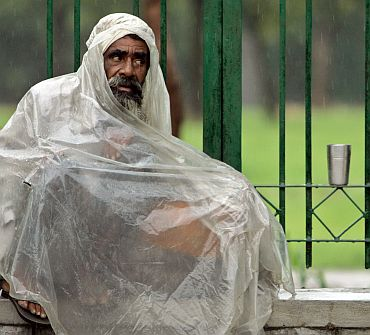 File photo shows a beggar covers himself with a polythene sheet on a street in New Delhi
