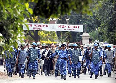 Paramilitary soldiers escort lawyers as they leave the high court in Lucknow on Sep 30, 2010
