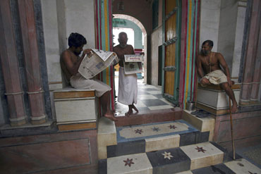 Priests read newspapers inside a temple in Ayodhya