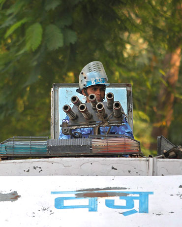 A security personnel keeps guard atop his armoured vehicle outside the high court in Lucknow