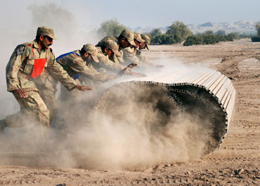 Pakistan soldiers unfold a temporary bridge during military exercises in Multan