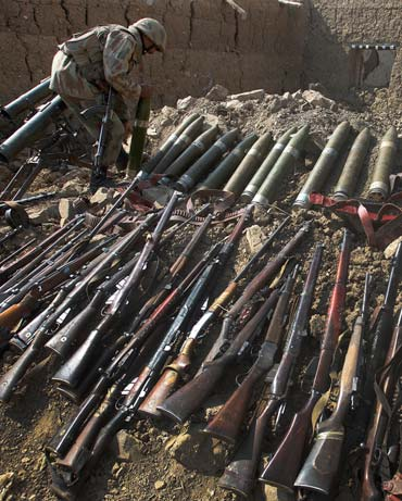 A Pakistan soldier with weapons and ammunition recovered during operations against the Taliban