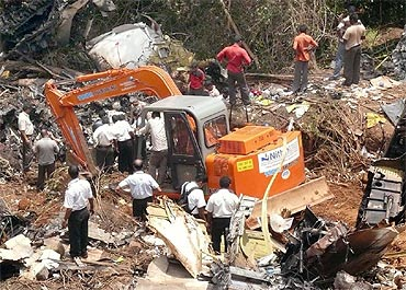 Rescuers try to dig out bodies from the crash debris following the mishap in Mangalore