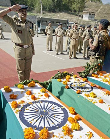 A CRPF officer salutes in front of coffins containing the bodies of slain colleagues