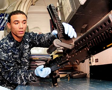 Gunner's Mate 2nd Class Edward P Oyola cleans an M-240B machine gun in the armory of the USS Essex