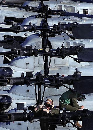 Maintenance work being done on the rotor of an AH-1Z Super Cobra helicopter aboard USS Essex