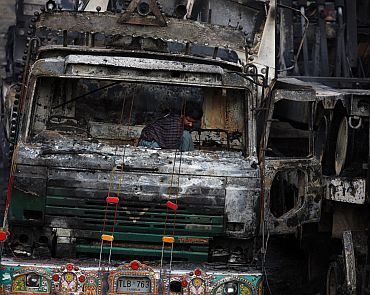 A man searches through a damaged truck, carrying supplies to foreign forces in Afghanistan, after it was attacked and burnt in a field in Sangjani, located in the outskirts of Islamabad