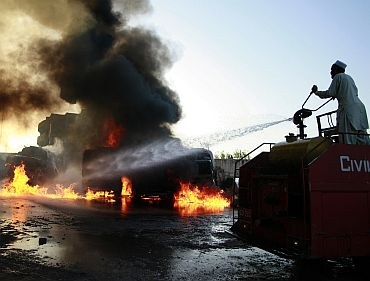 A man tries to extinguish a fire after fuel trucks were set aflame in Peshawar