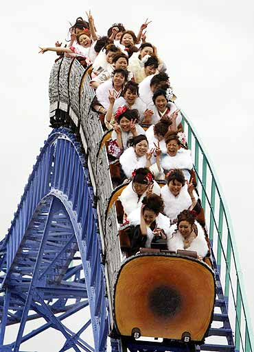 Japanese women ride a roller-coaster at Toshimaen amusement park in Tokyo