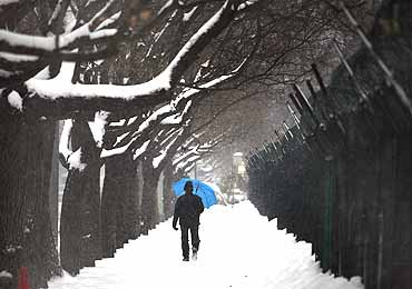 A man walks along a icy footpath