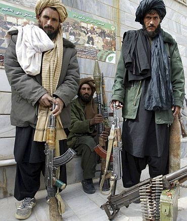 Taliban militants pose for pictures after they join reconciliation program with the Afghan government, in Herat