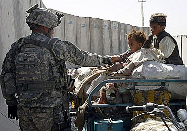 A US soldier greets children while their father is being checked at a joint military checkpoint in Kandahar