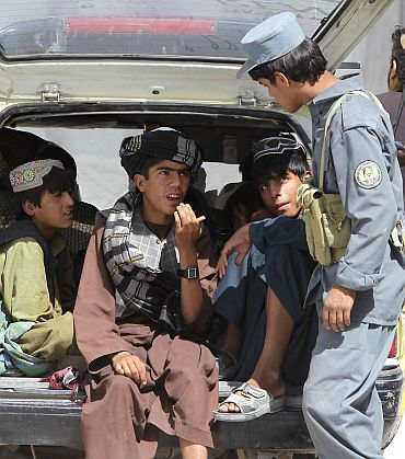An Afghan policeman interrogates passengers of a vehicle at a joint military checkpoint near Kandahar
