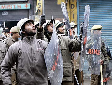Policemen with protective shields at a protest in Kashmir