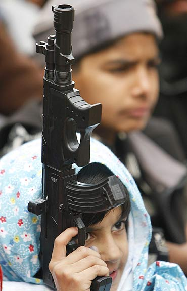 A young Jamaat-e-Islami supporter with a toy gun at a protest in Srinagar