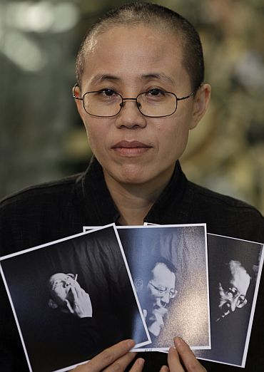 Liu Xia, the wife of Chinese dissident Liu Xiaobo, holds photos of Liu Xiaobo during an interview in Beijing on October 3