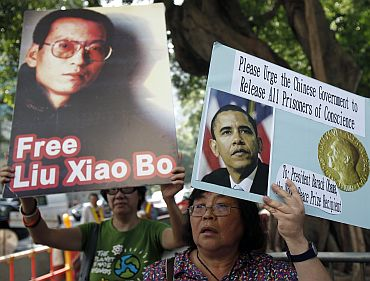 A demonstrator holds a picture of Chinese dissident Liu Xiaobo during a protest, urging Nobel peace prize recipient and US President Barack Obama to demand the Chinese government to release all dissidents, outside the US Consulate General in Hong Kong