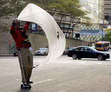 Richard Coit uses a sheet of plastic as a sail to propel himself on his scooter on a windy day in Boston, Massachusetts on October 7