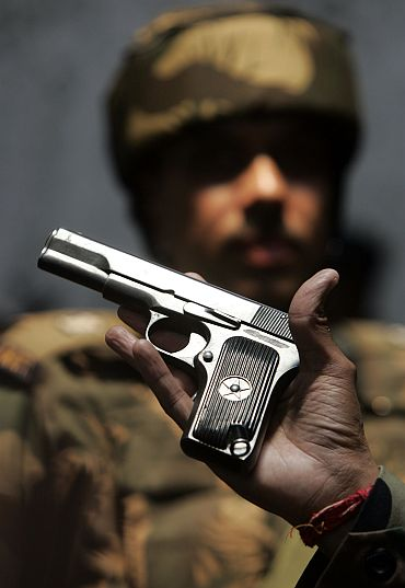 Indian army officer shows a seized pistol after a gun battle with Laskar militants to media in Kupwara, Kashmir