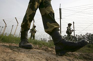 Border Security Force soldiers patrol the fenced border with Pakistan near Jammu