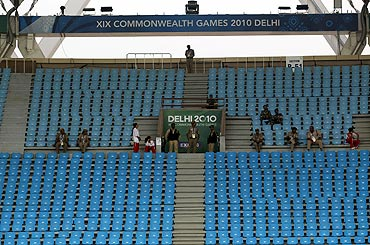 Security and volunteers sit in some empty seats at the Jawaharlal Nehru Stadium