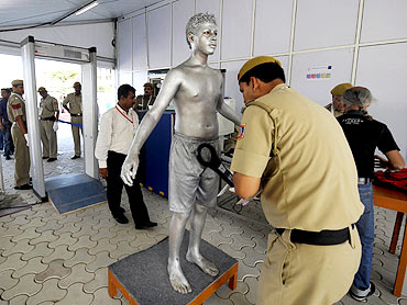 An artist goes through a security check before his performance at the Commonwealth Games athletes Village in New Delhi