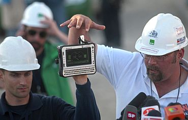 Engineer Ben Morris (Left) of the US and Chilean medical doctor Jean Romagnoli show journalists a gauge that will be used to monitor the vital signs of the trapped miners as they are lifted individually to the surface in a capsule
