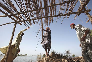 Villagers displaced by floods build a makeshift tent in Sindh province