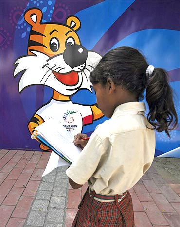 A schoolgirl makes a drawing of the mascot of the Commonwealth Games