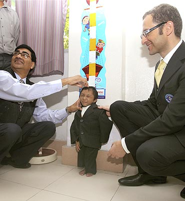 Khagendra Thapa's height is measured by Dr Hom Neupane (Left) in the presence of Guinness Book of World Records representative Marco Frigatti (Right) in Pokhara, west Nepal
