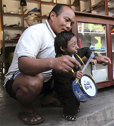 Thapa and his father Rup Bahadur Thapa play with a birthday gift given to Khagendra at his rented house in Pokhara
