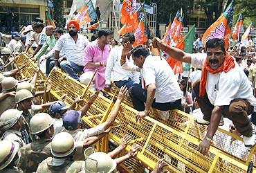 BJP activists shout slogans as police try to stop demonstrators during a protest against price hike in Lucknow