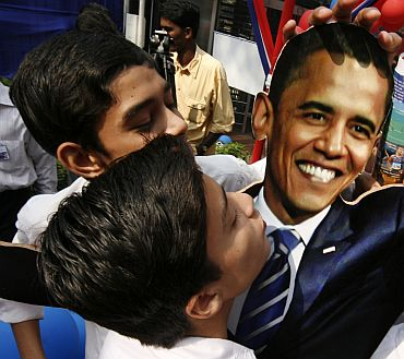 Students reach out to kiss a cutout of Obama at the American Centre in New Delhi