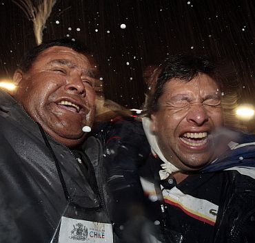 Relatives of miners celebrate after the last miner Luis Urzua was hoisted up to the surface at the San Jose mine in Copiapo on October 13