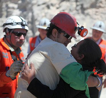 Trapped miner Daniel Herrera (red hard hat) hugs his wife after reaching the surface to become the 16th to be rescued from the San Jose mine in Copiapo