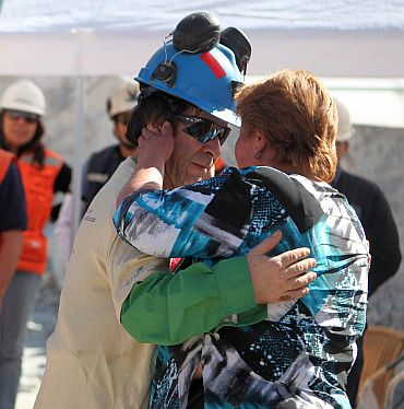 Trapped miner Johnny Barrios hugs his girlfriend Susana Valenzuela after reaching the surface to become the 21st to be rescued from the San Jose mine in Copiapo