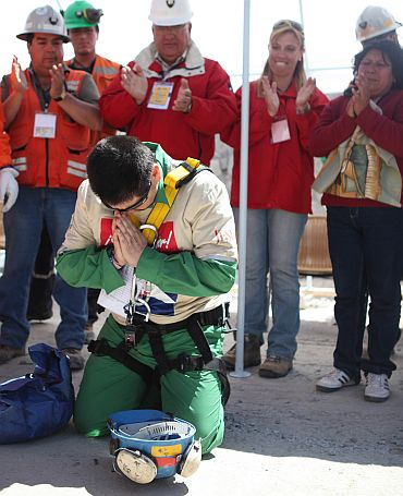 Trapped miner Esteban Rojas kneels to pray after reaching the surface as he became the 18th to be rescued from the San Jose mine in Copiapo