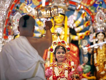 A priest worships a girl dressed as goddess Durga on Kumari Puja, one of the biggest attractions of the festival