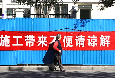 A woman walks past a banner reading, 'sorry for the inconvenience due to the construction' which is located at the entrance of a residential compound where Liu Xia, the wife of Chinese dissident and Nobel Peace Prize winner Liu Xiaobo, lives in Beijing