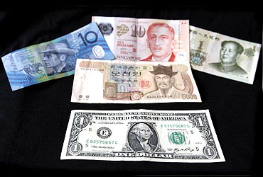 A US dollar note is pictured alongside other currencies including the Australian Dollar, Singapore Dollar, Korean Won and China's Yuan