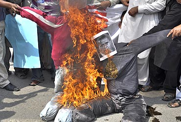 Pakistani protesters burn effigies of US President Barack Obama and former Pakistani President Pervez Musharraf, during a protest in Multan, to condemn the verdict against Aafia Siddiqui. A US judge imposed an effective life term of 86 years on Pakistani neuroscientist Siddiqui convicted of shooting at FBI agents and soldiers after her arrest in Afghanistan
