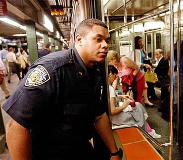 New York Police Department Officer Ariel Ortiz, left, looks into a train as he patrols the Times Square subway station in New York on Thursday