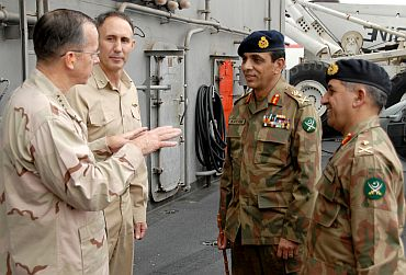 (From Left) US Navy Adm Mike Mullen, chairman of the Joint Chiefs of Staff, and US Navy Rear Adm Scott Van Buskirk, commander of Carrier Strike Group 9, talk with Pakistani Army Gen Ashfaq Kayani, chief of army staff, and Pakistani Army Major Gen Ahmad Shuja Pasha, director general of military operations, on the flight deck aboard USS Abraham Lincoln in the North Arabian Sea
