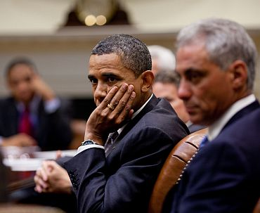 Obama with Chief of Staff Rahm Emanuel (right) listens during an economic briefing in the Roosevelt Room of the White House