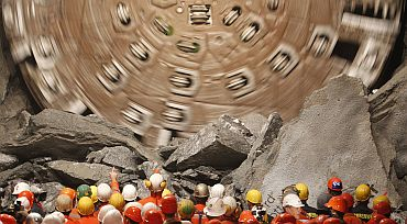Miners watch as the drill machine 'Sissi' breaks through the rock at the final section Faido-Sedrun, at the construction site of the NEAT Gotthard Base Tunnel on October 15. With a length of 57 km crossing the Alps, the world's longest train tunnel should become operational at the end of 2017