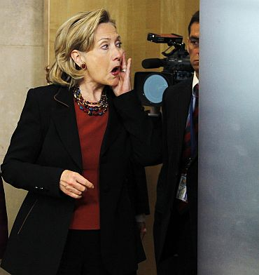 US Secretary of State Hillary Clinton adjusts her make-up before a news conference at the EU Commission headquarters in Brussels
