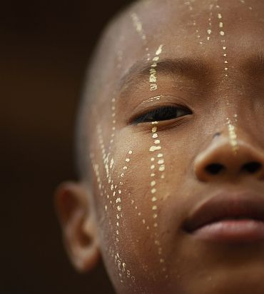 A boy with his face decorated with thanaka paste waits outside a local school, for children of migrant workers from Myanmar, near Mae Sot in northwest Thailand on October 15. Myanmar's long standing political crisis has forced millions of people across the border for a better and safer life. Some 140,000 refugees live in official camps along the Myanmar-Thailand border, according to the UN refugee agency and there are concerns that hostilities in the hills of eastern Myanmar could intensify as a result of a refusal of several ethnic political groups to take part in an election next month